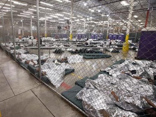 children on cots in a large cage at ICE internment center