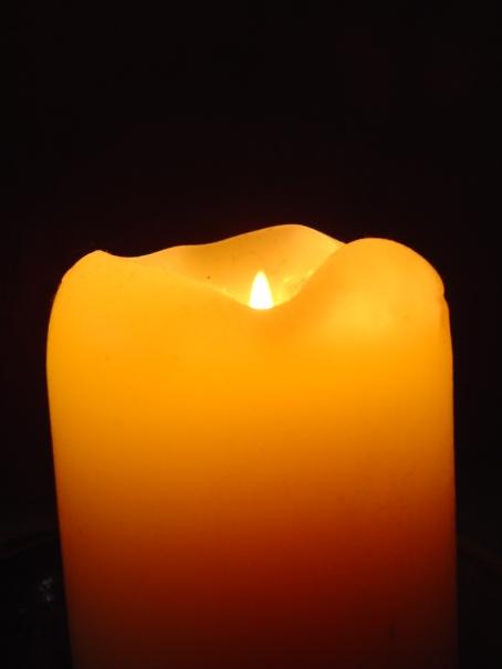orange candle burning against a black background