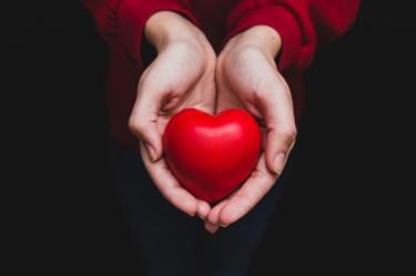 hands-holding-heart-dark-background_23-2147596663