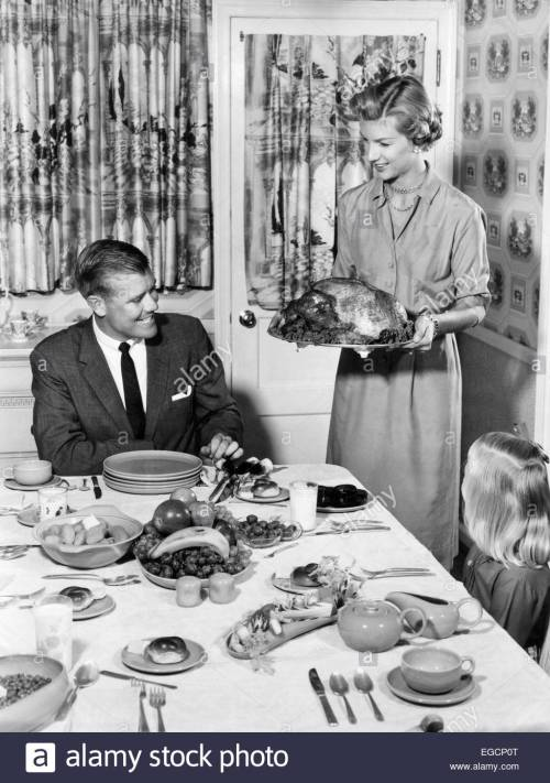 1950s-thanksgiving-family-at-dining-room-table-mom-holding-turkey-EGCP0T
